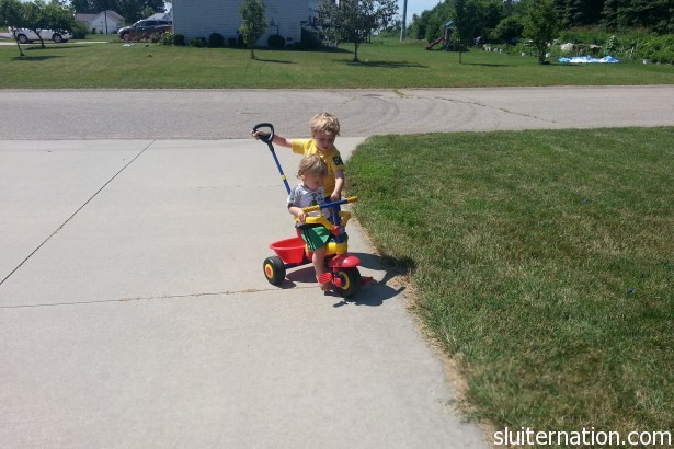 "June 28: Eddie ""teaches"" Charlie about riding the trike."